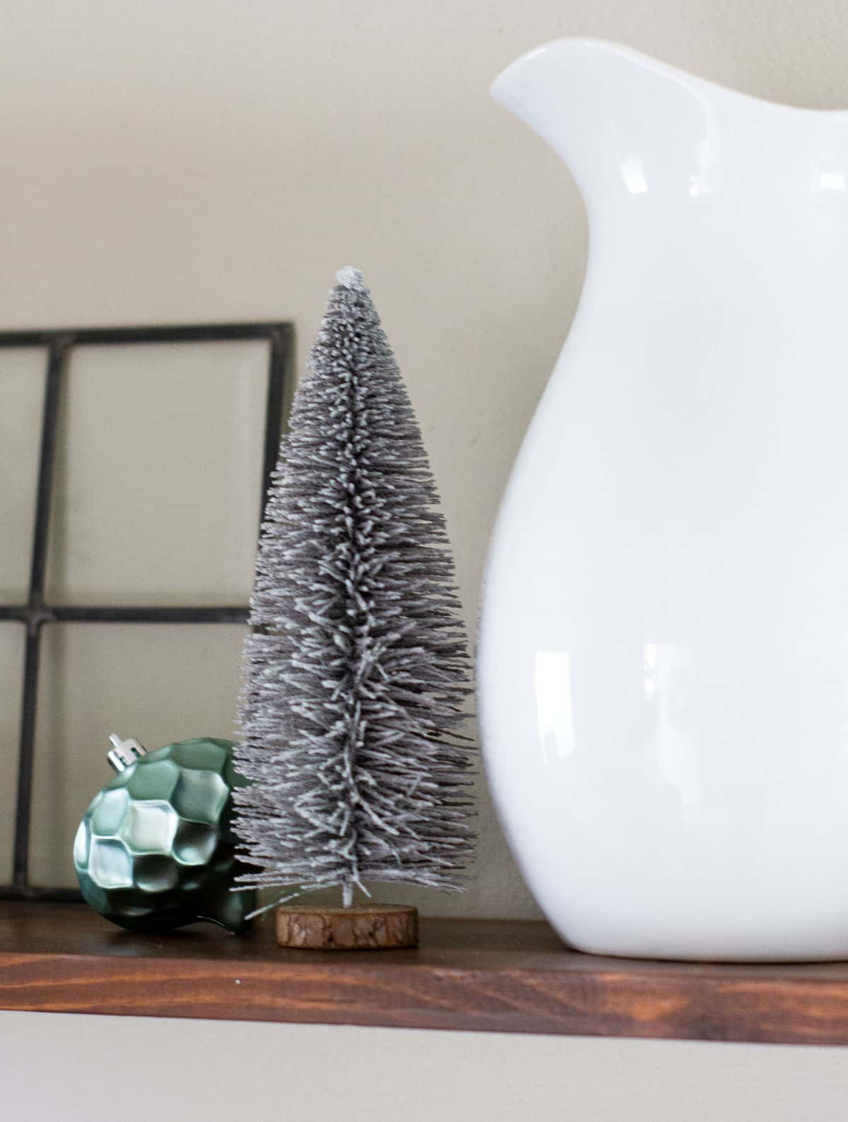 frosty minty christmas trees bottle brush trees with ornament sitting next to white pitcher on shelf