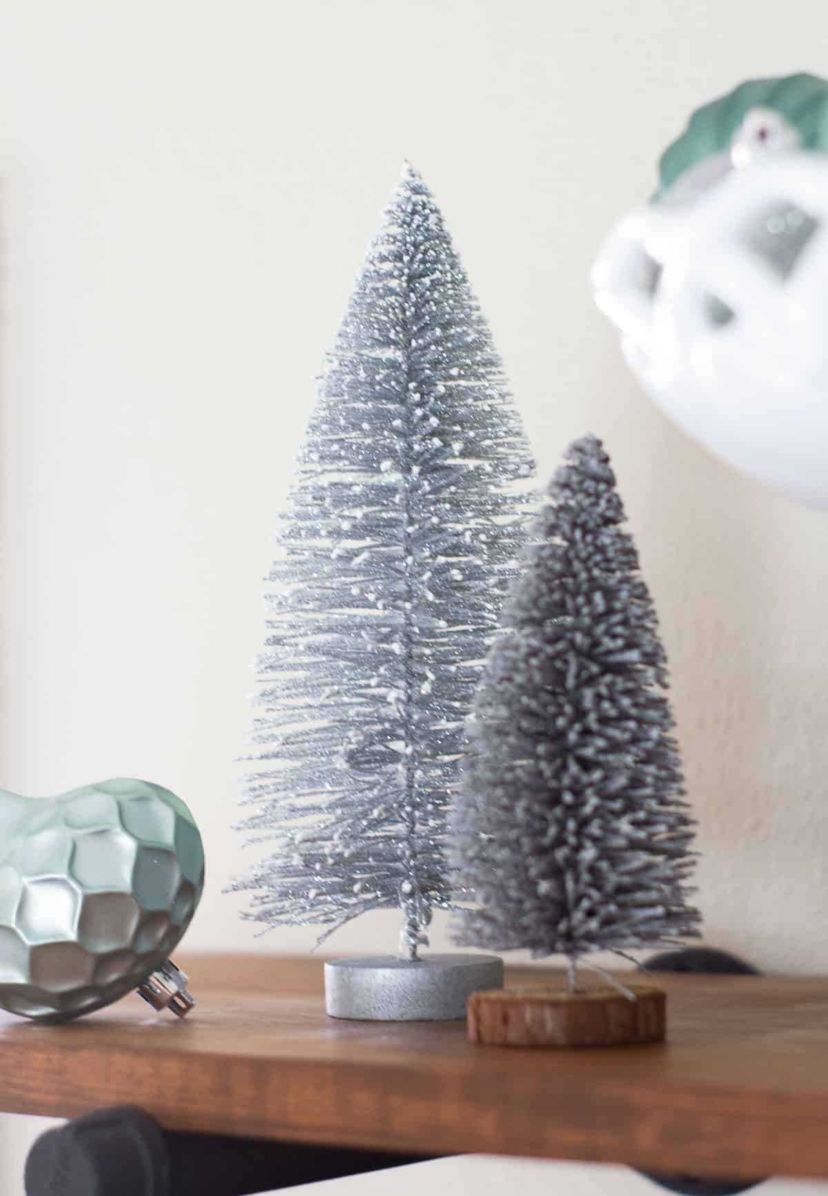 sparkly bottle brush tree with ornaments on shelf