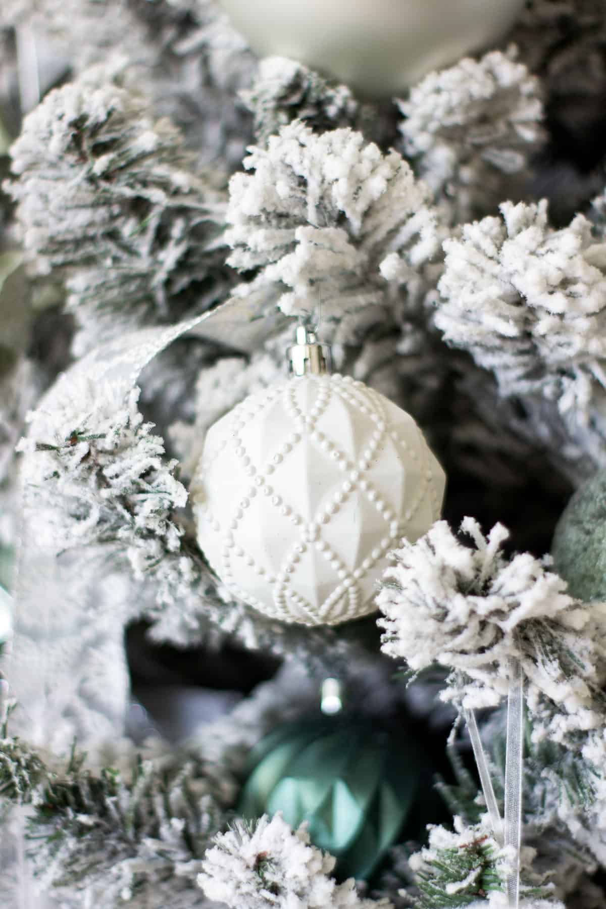 white textured ornament in flocked tree