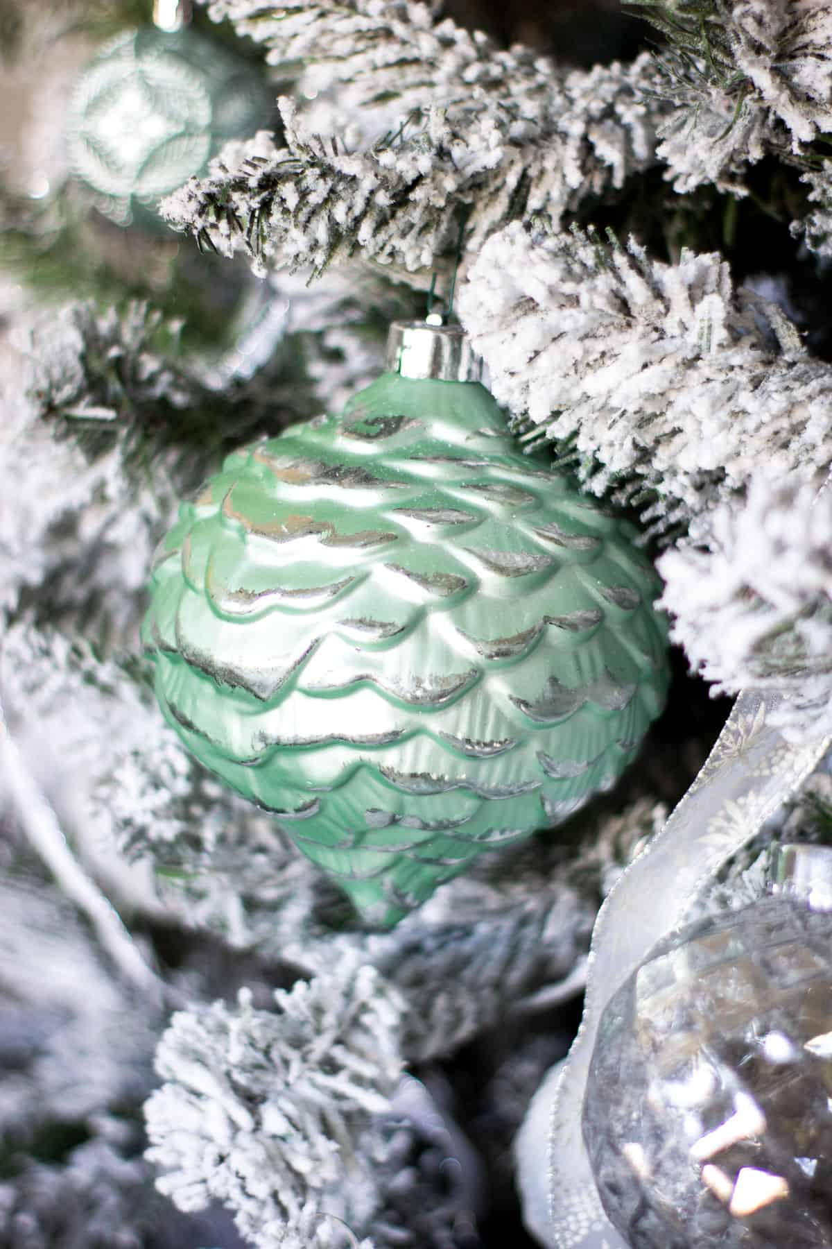 mint pinecone ornament on flocked tree