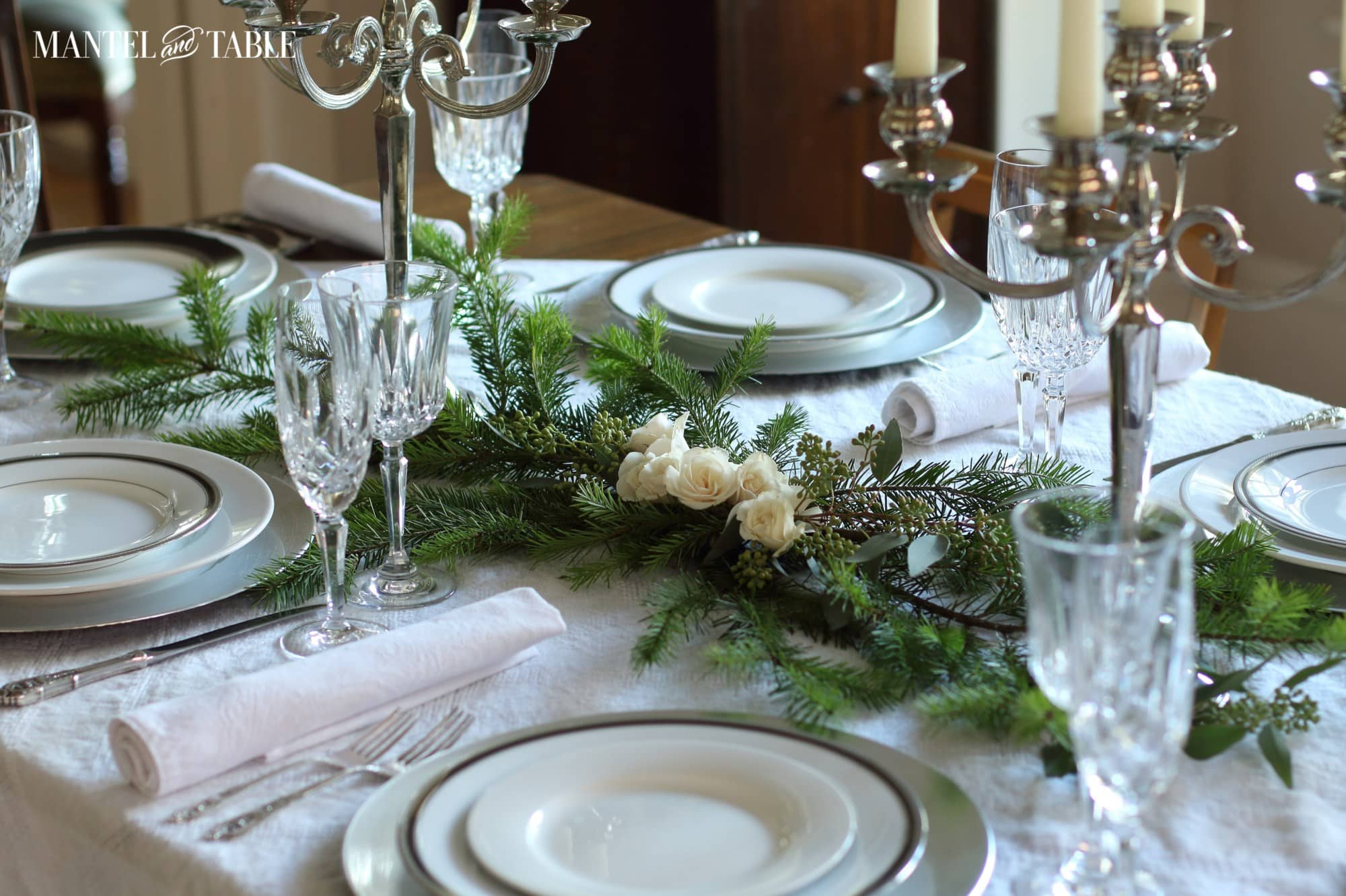 roses and evergreen centerpiece with simple white place settings and crystal