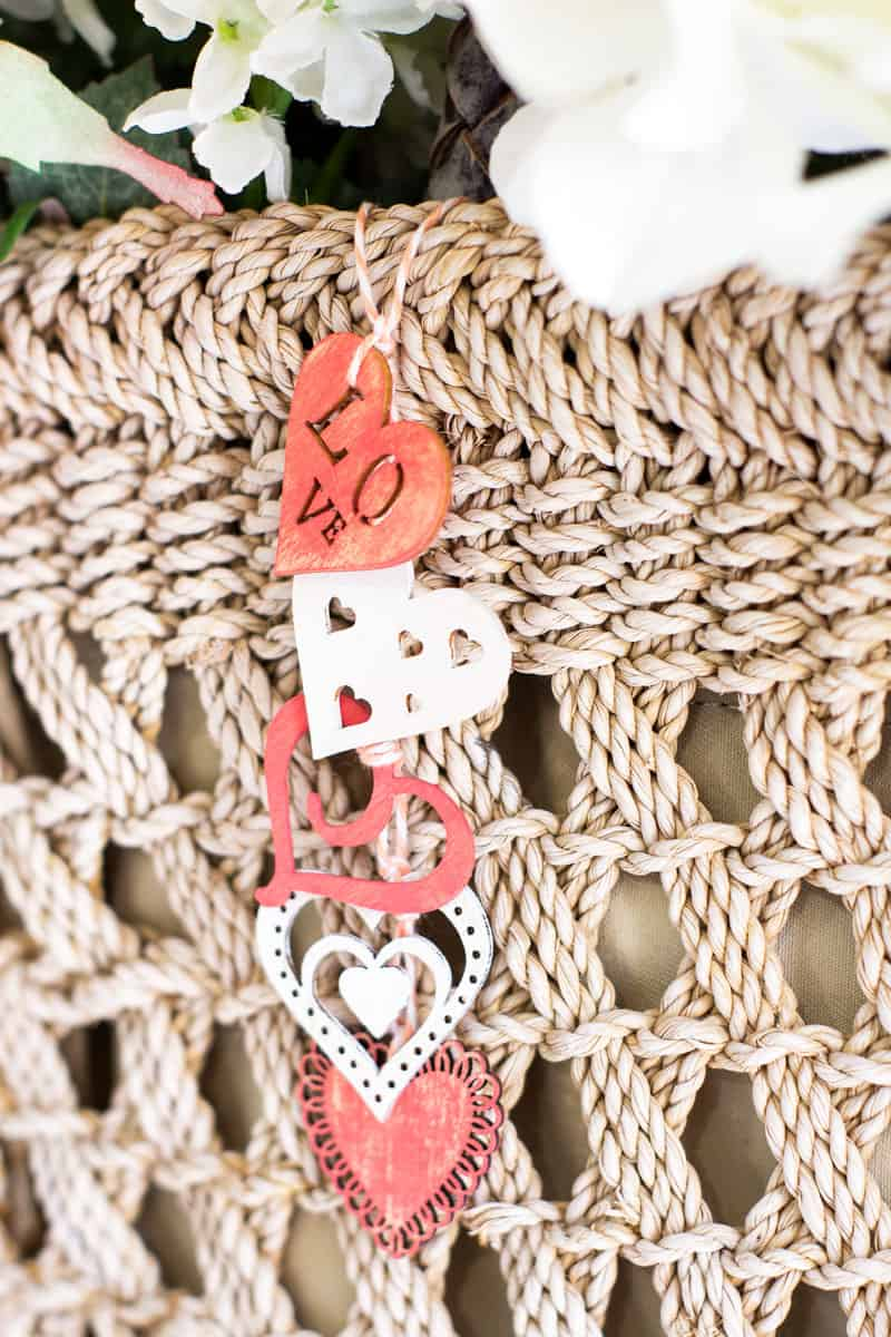 string of wood hearts painted in peach and white on woven background