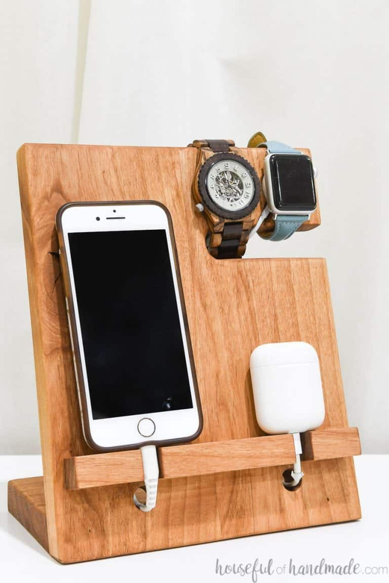 wood docking station with smart phone and watches on nightstand