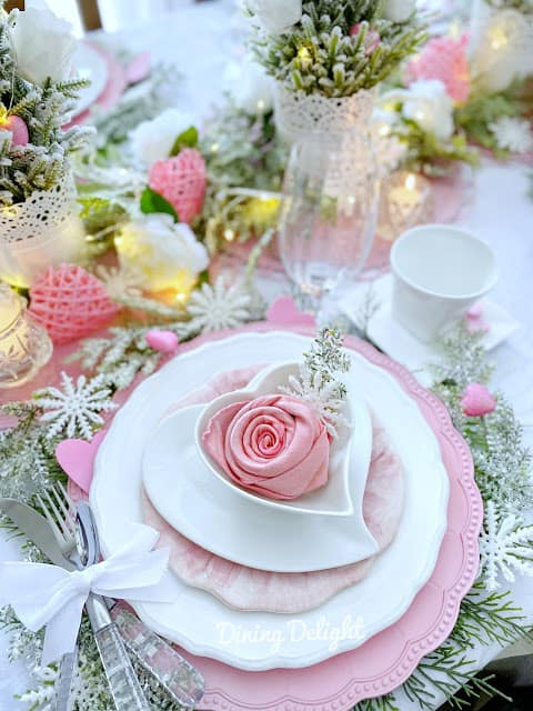tuesday turn about 87 pink white and green valentine tablescape with dinner plates and stemware.