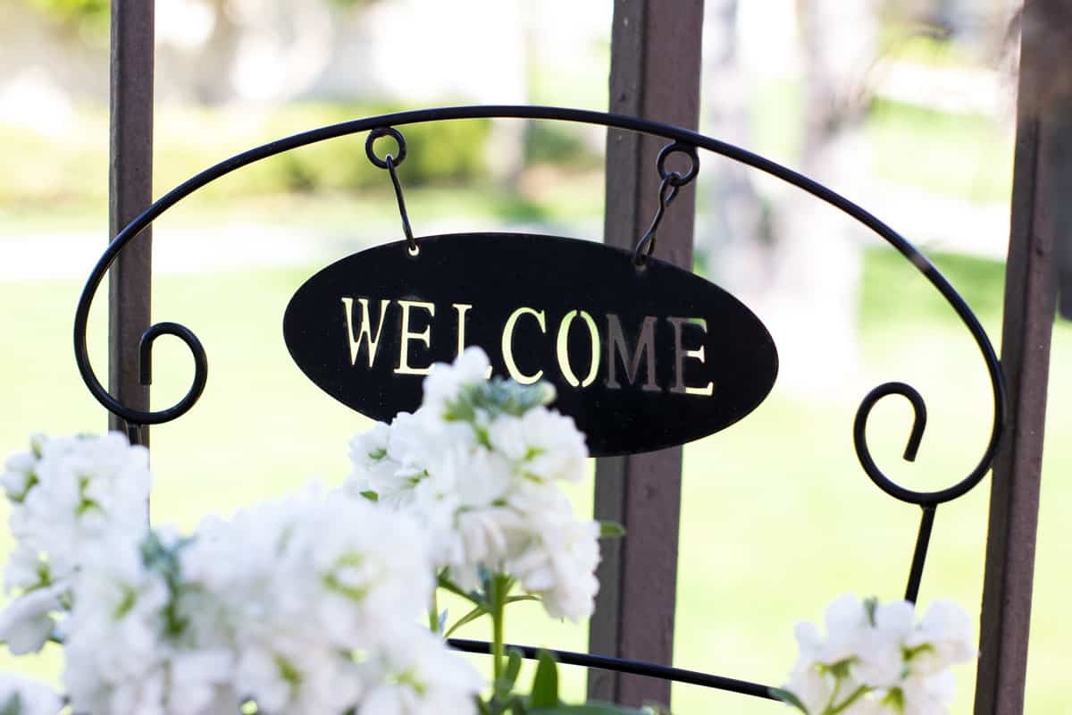 small spring porch welcome sign with white flowers
