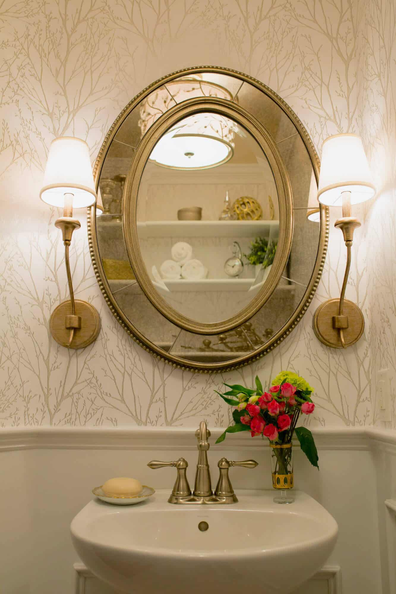 gold mirror on bathroom wall with sconces and graphic wallpaper