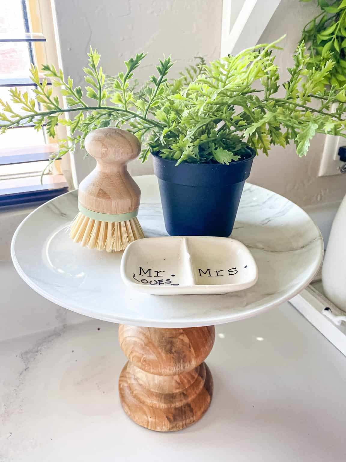 diy cake stand with brush dish and plant on kitchen counter