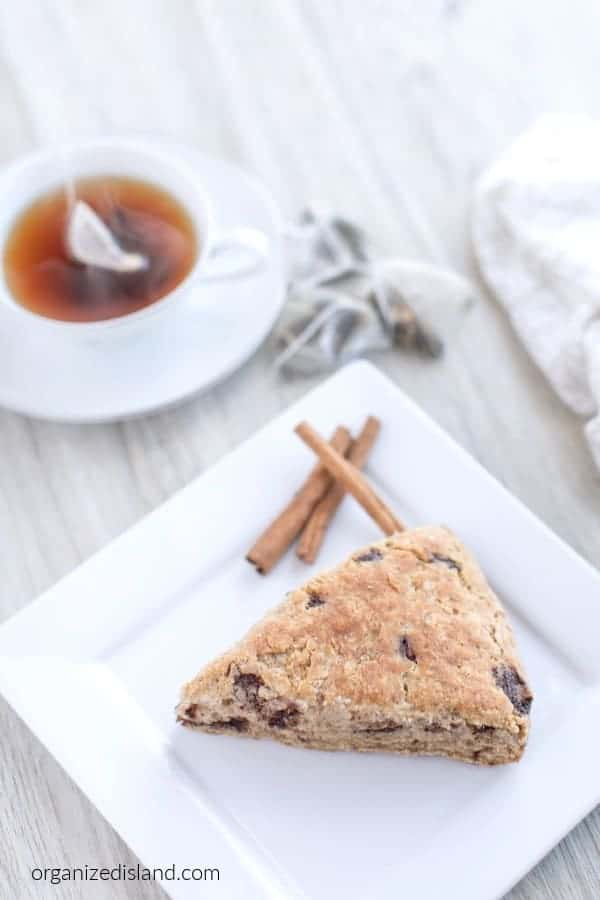 cinnamon scone on plate with cinnamon sticks and tea on white dishes