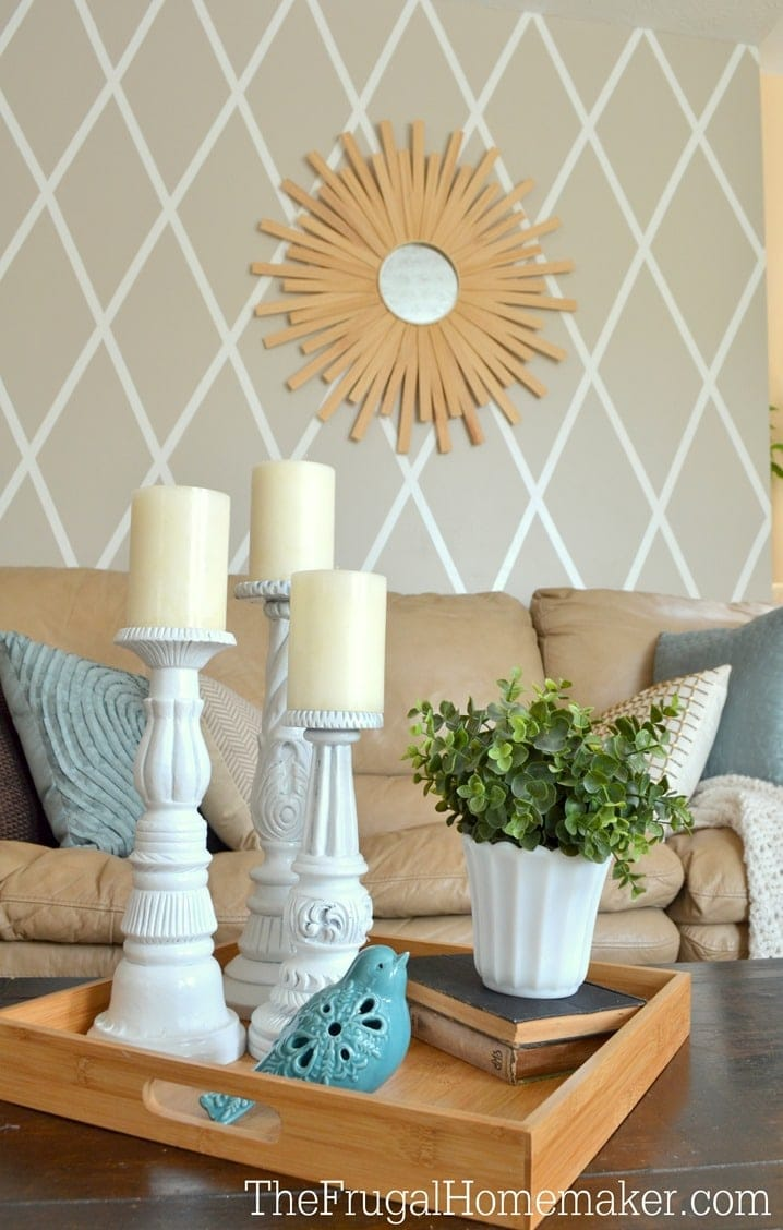 accent wall with sunburst mirror and decor items in forefront