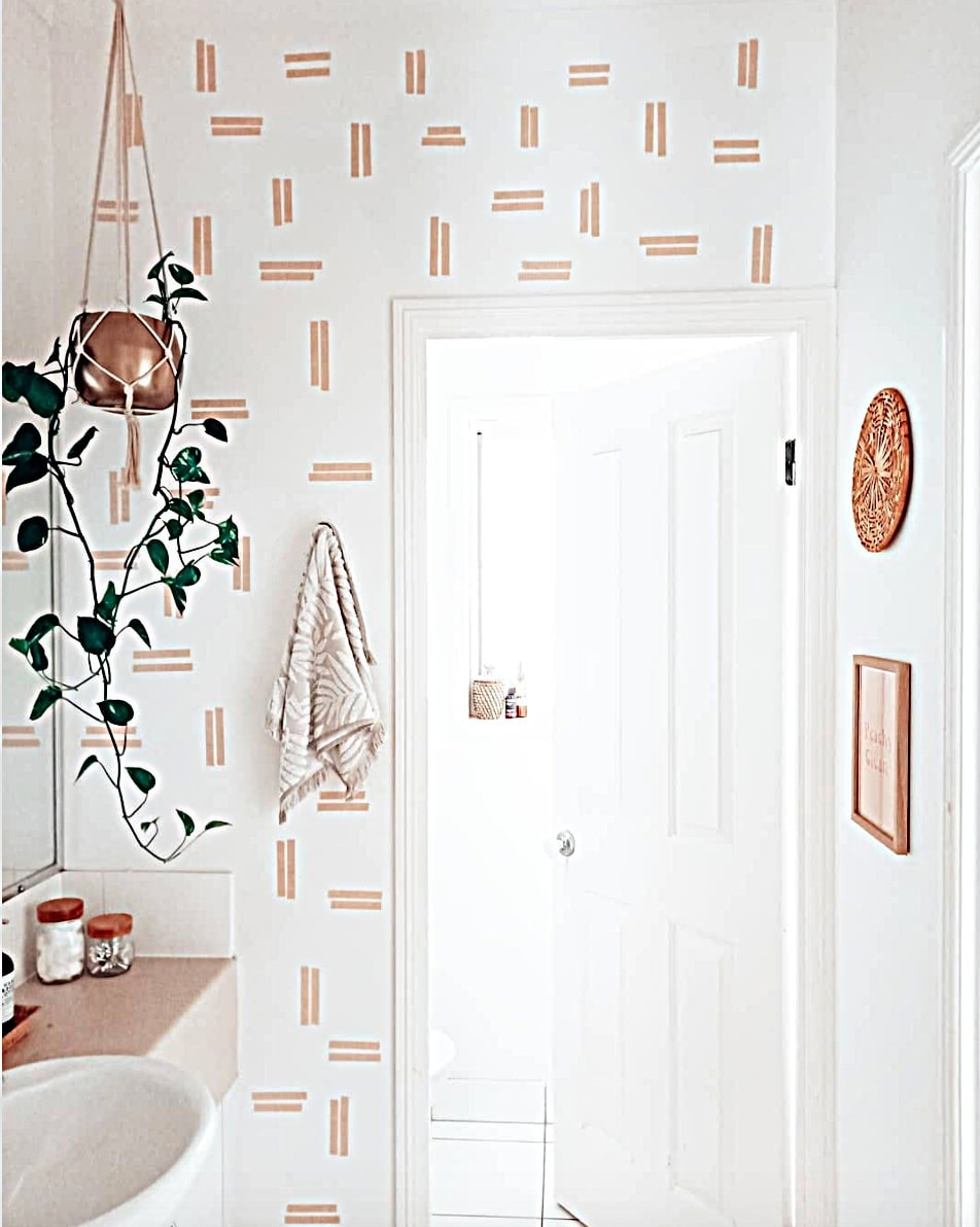 temporary wall coverings for your apartment bathroom with wall accented in washi tape and hanging plant