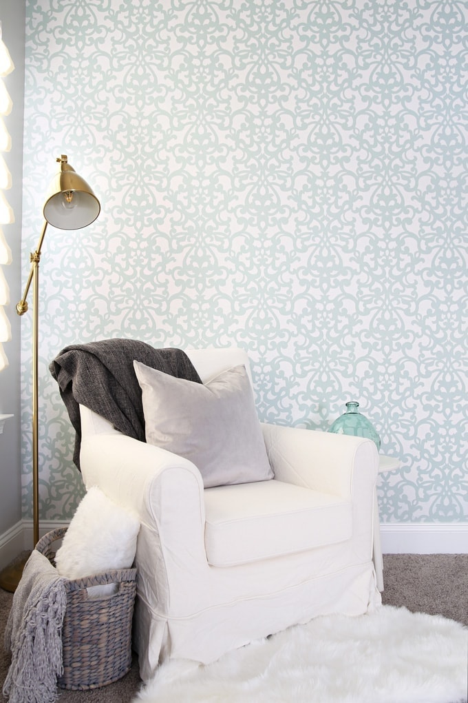 stenciled wall with cozy chair and lamp