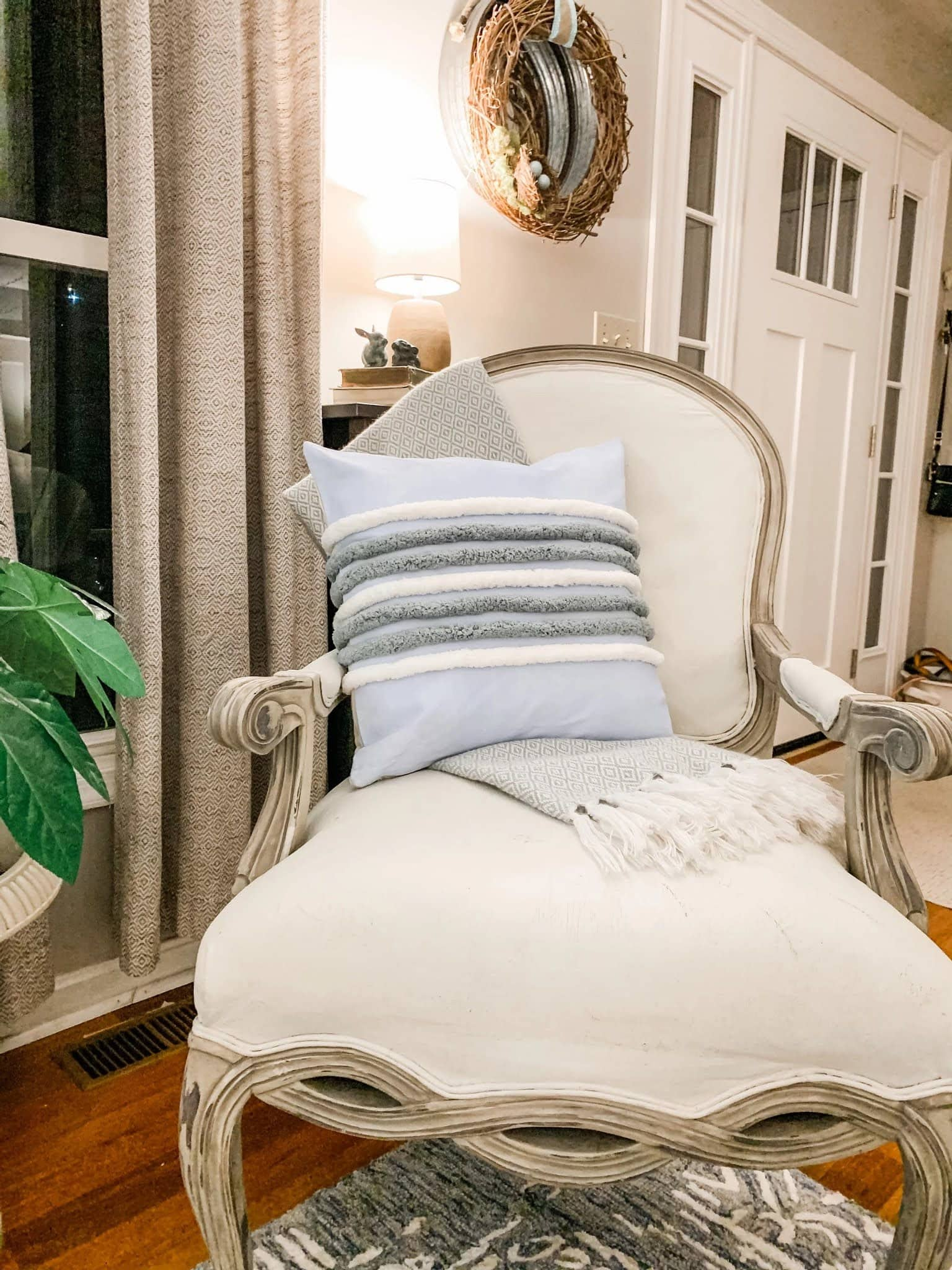 chair with pillow and throw blanket in living area