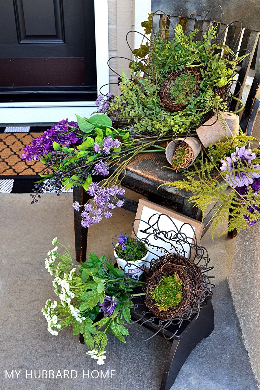 patio with purple flowers greenery and a bench