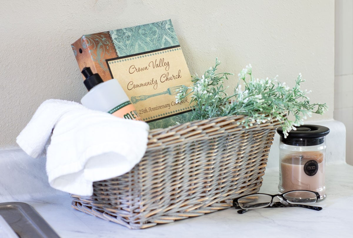 diy chippy paint thrifted basket with towel cookbook and soap with a candle on the side