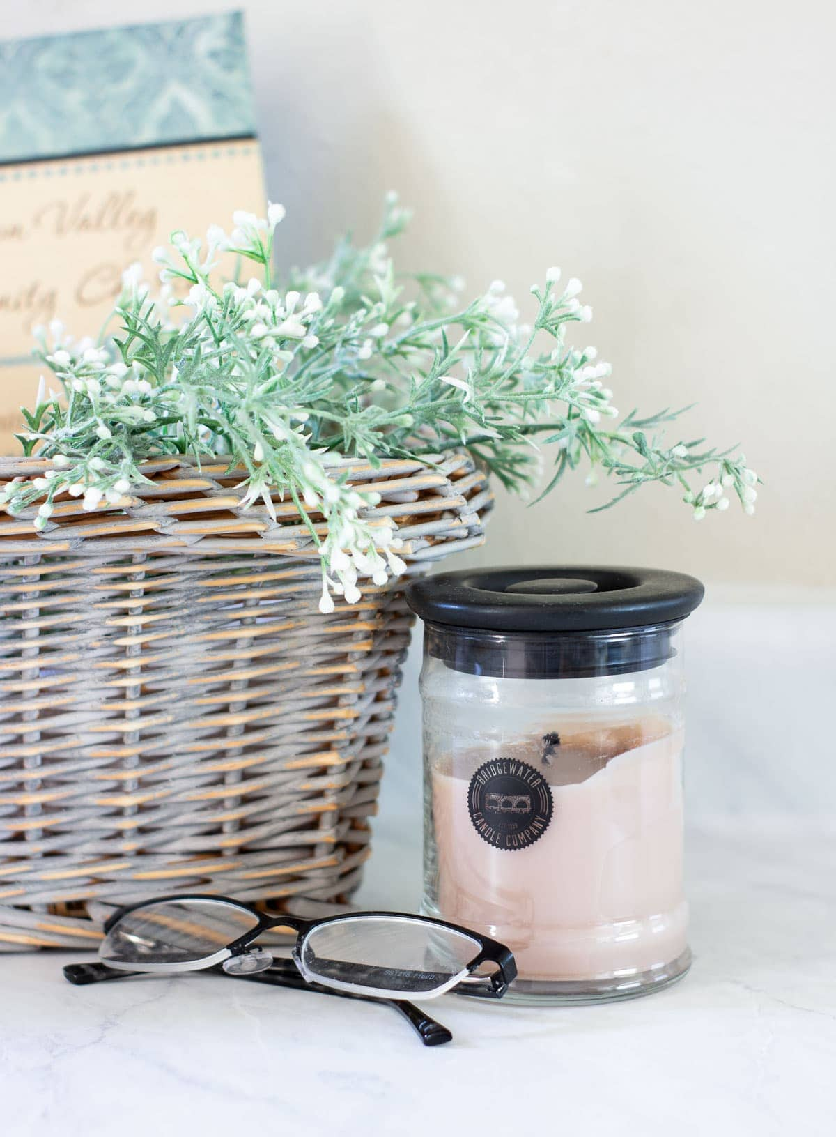 candle with basket and flowers and glasses
