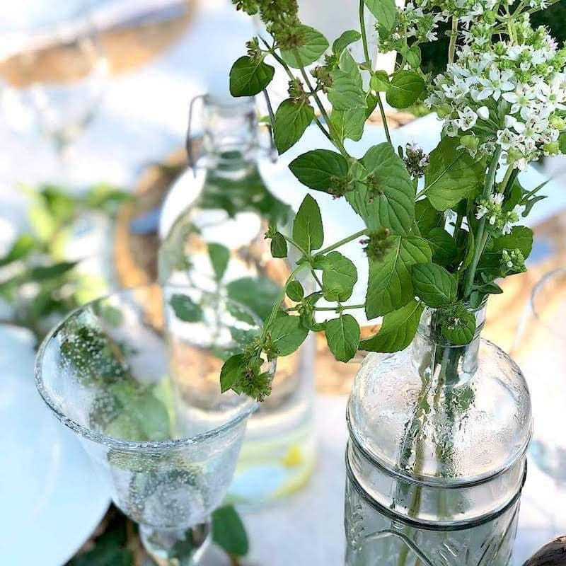 fresh herbs in a clear bottle on a light and fresh table