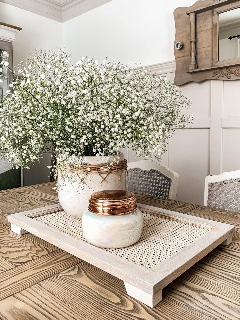 caned tray with pot of baby's breath and copper accents on table