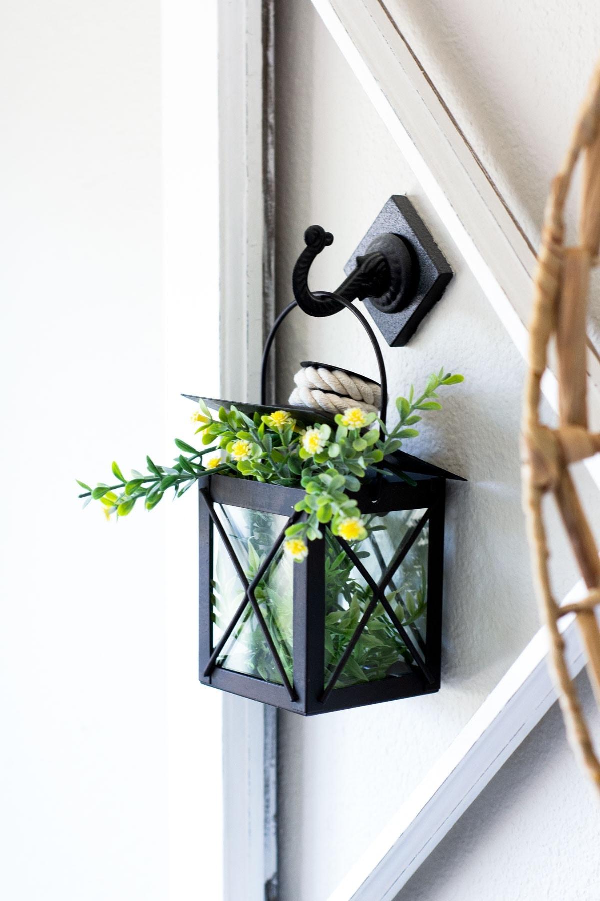 black mini lantern with yellow flowers greenery