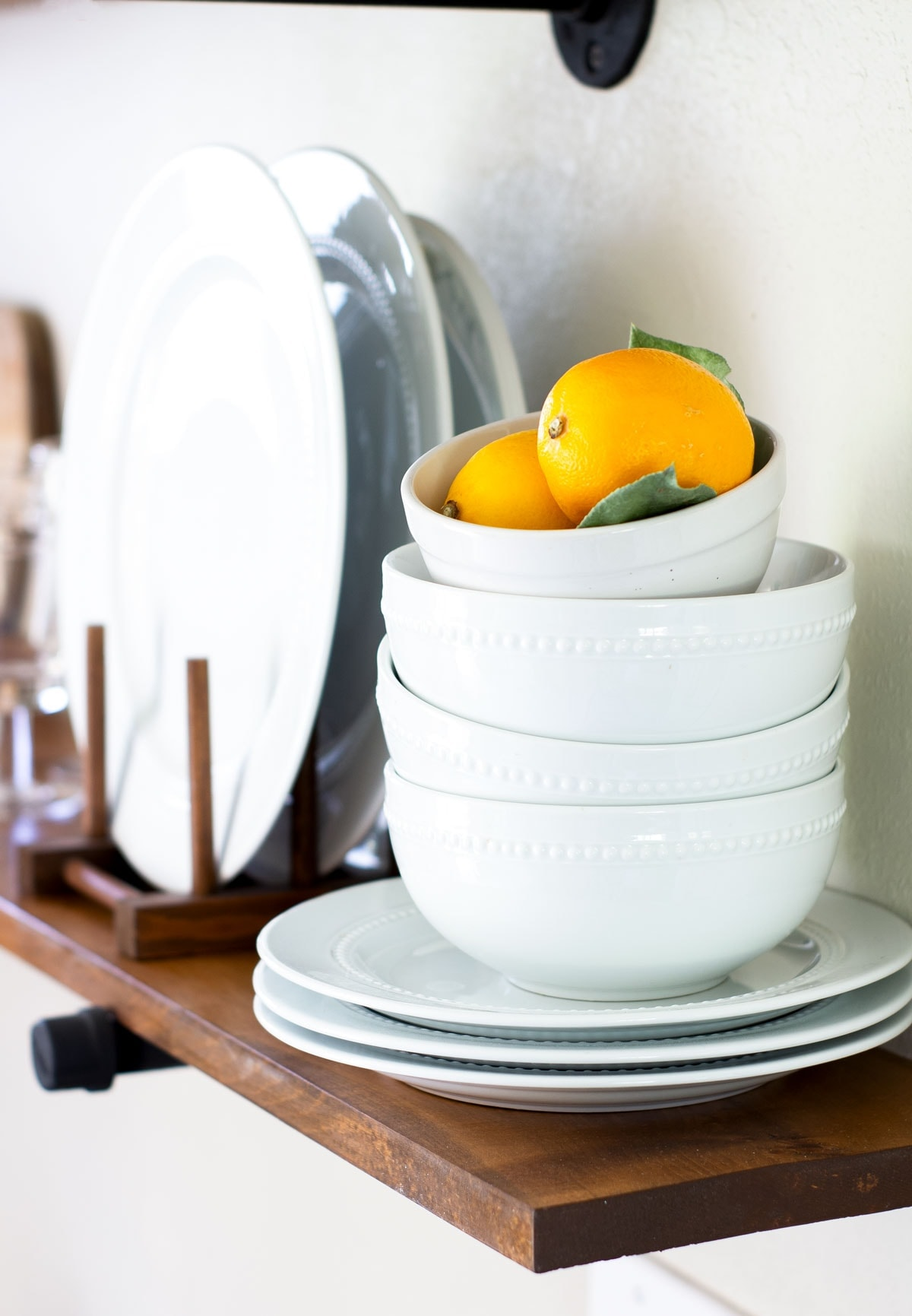 lemons in a stack of bowls on an open wood shelf