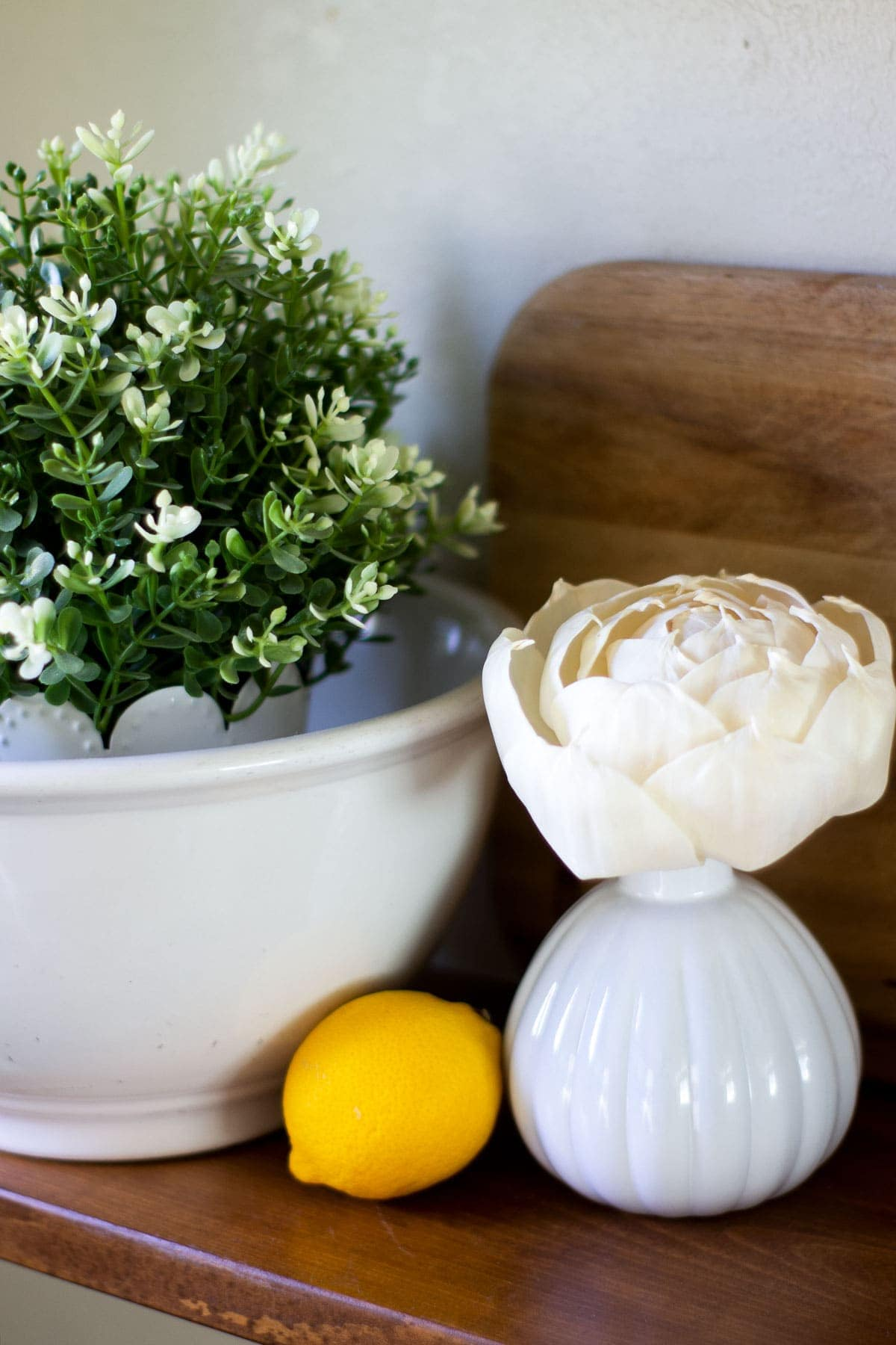 flower diffuser on shelf with lemon and ironstone bowl with greenery