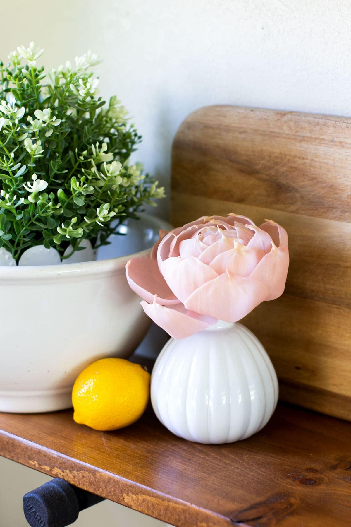 pink flower diffuser on shelf with lemon and ironstone bowl with greenery