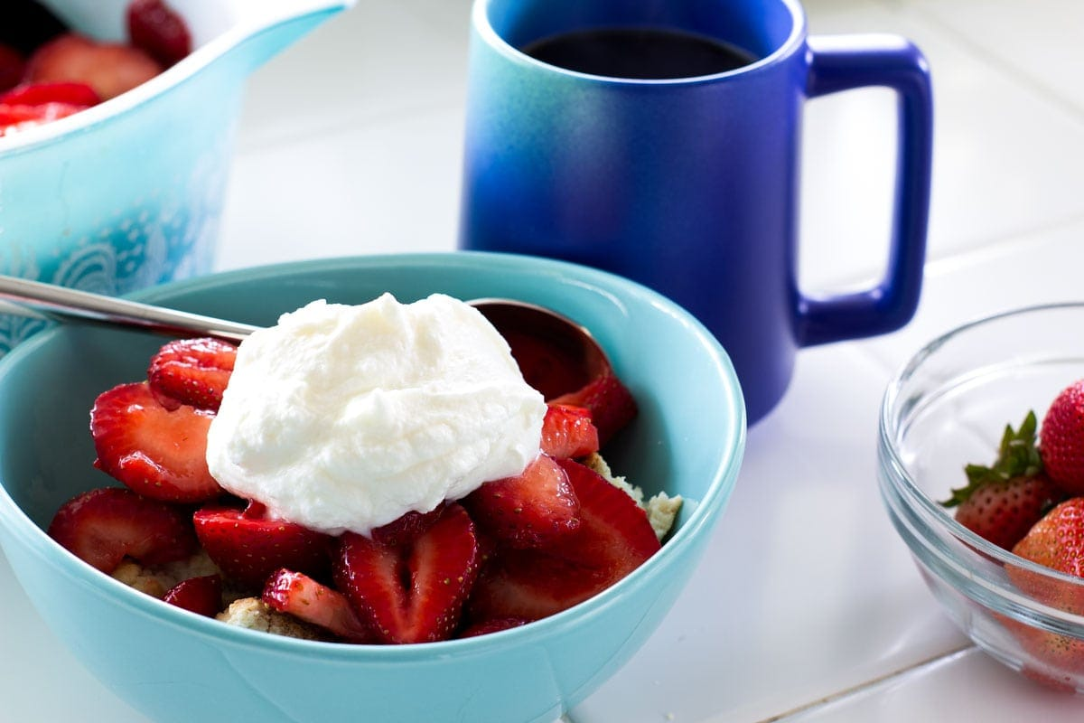 easy no fail strawberry shortcake in aqua bowl on tile counter with bowl of strawb