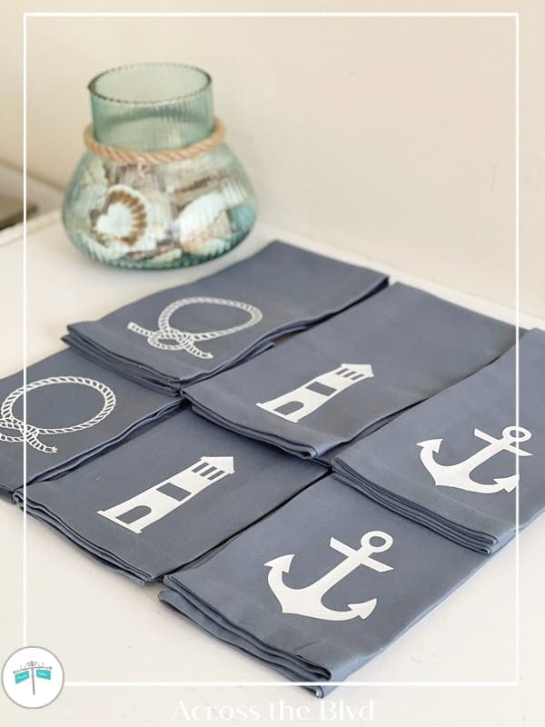 blue linen nautical napkins with a vase of shells on a white surface
