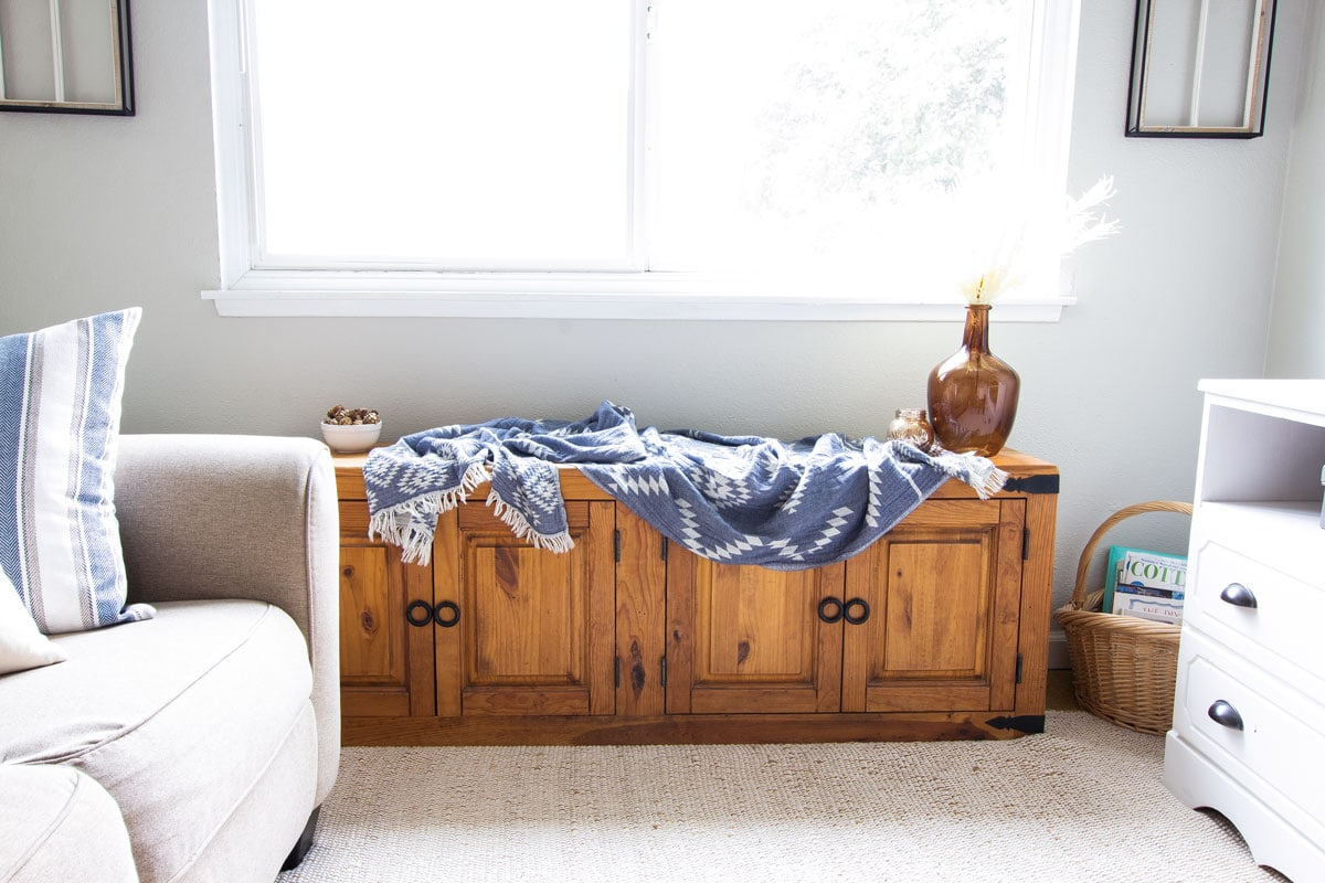 window bench with blue throw and amber bottle