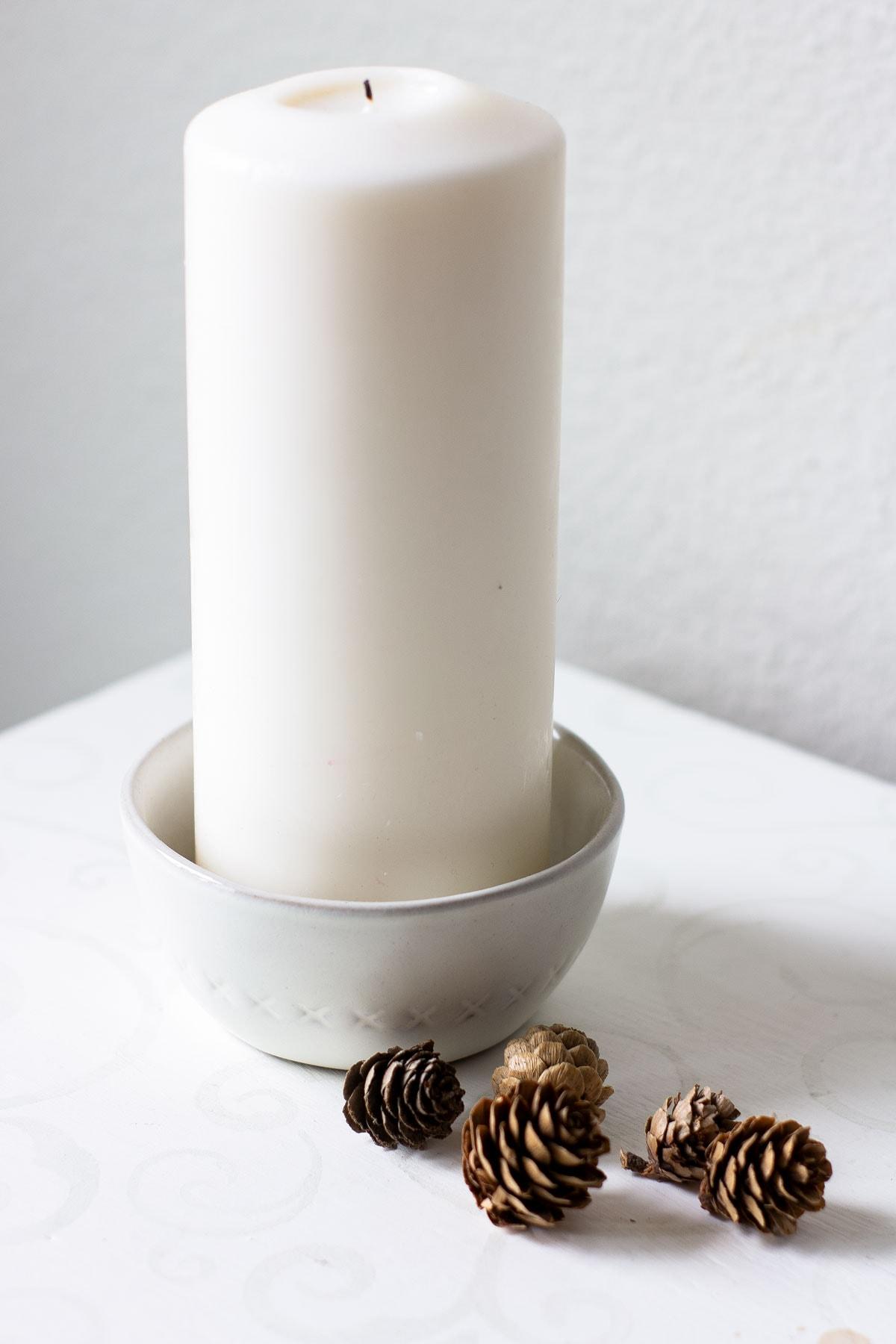 pillar candle in ceramic bowl with mini pine cones