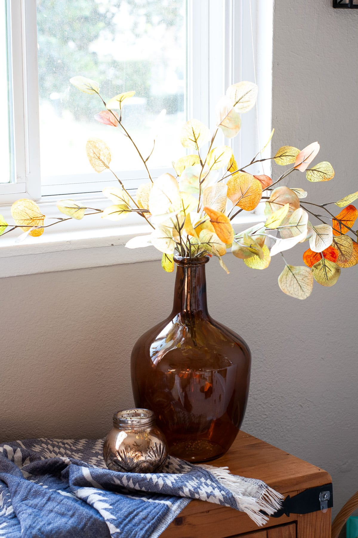 easy fall decor ideas amber demijohn with ivory stems on a window bench