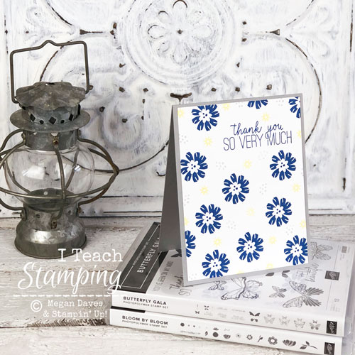 floral thank you card on books with lantern on wood surface