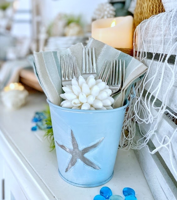 starfish canister with forks and napkins and beach decor