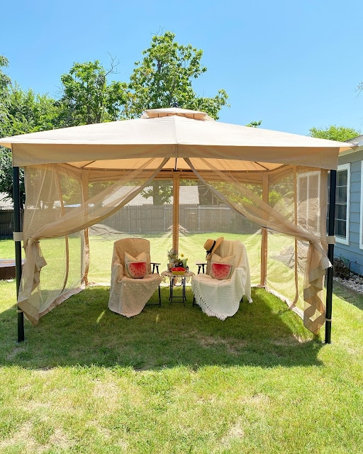 outdoor screened in gazebo with chairs and table