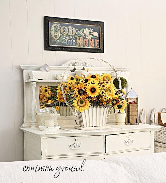 sunflowers in a basket on a dresser