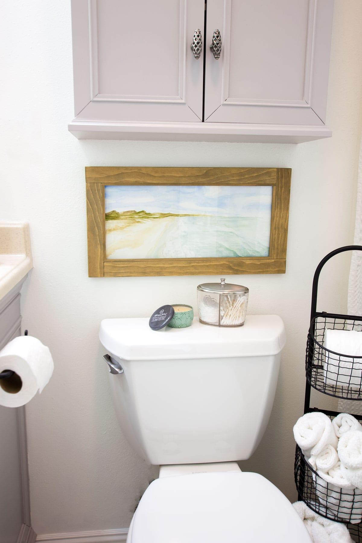 watercolor painting above toilet in bathroom