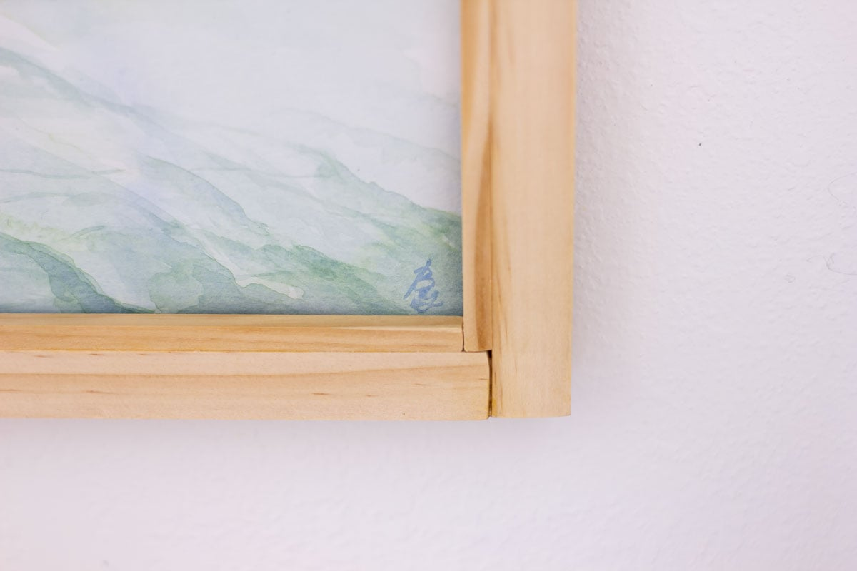 close up of custom wood frame with glass inset