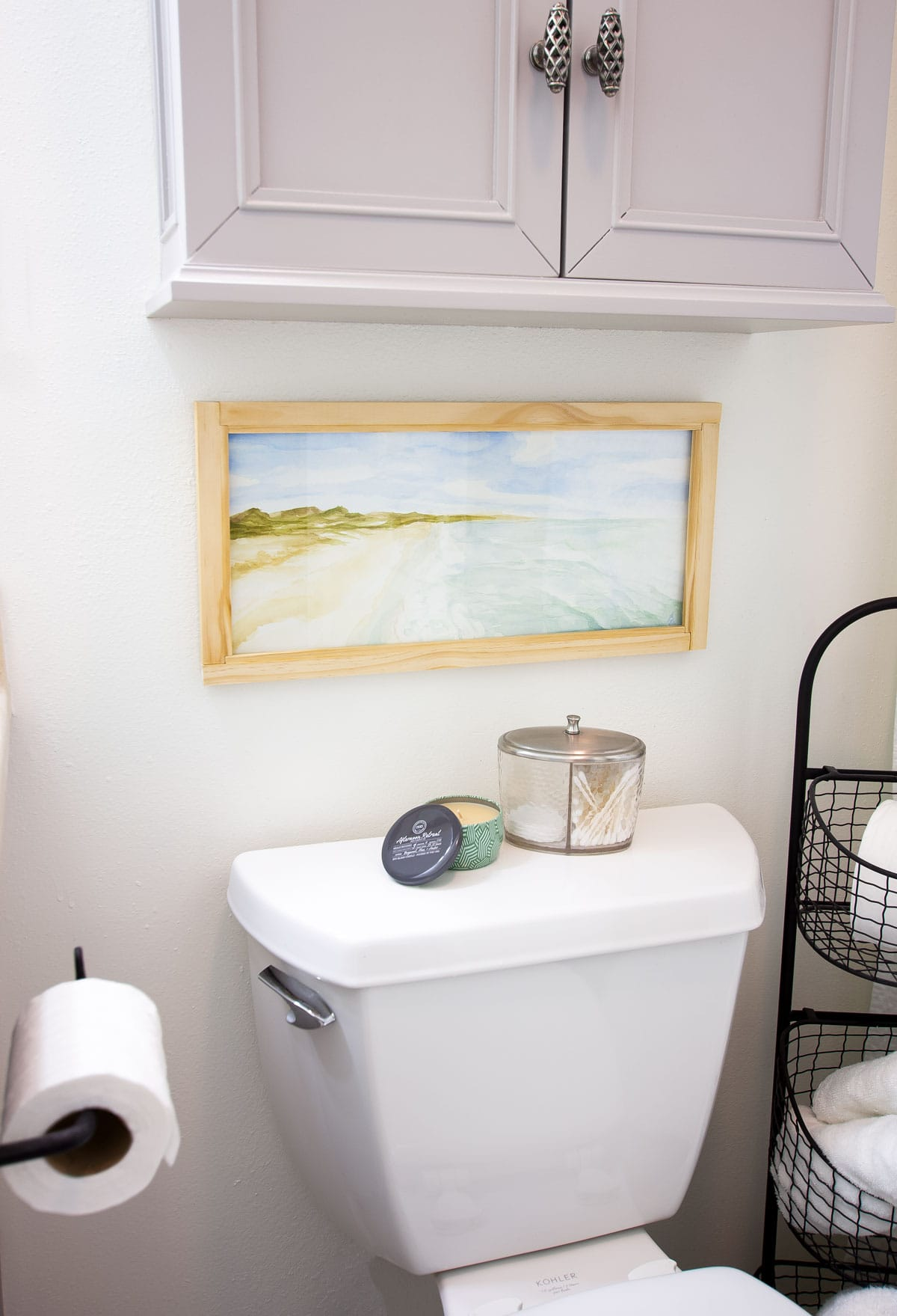 watercolor painting above toilet in bathroom with other bathroom items