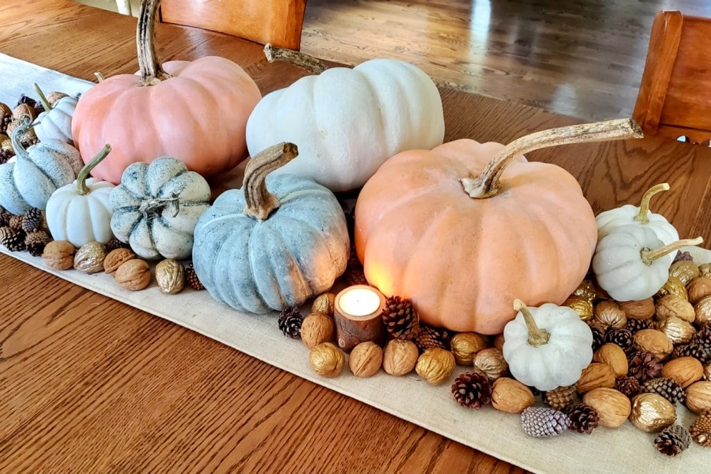 pumpkins on a tray with variety of nuts and tea lights