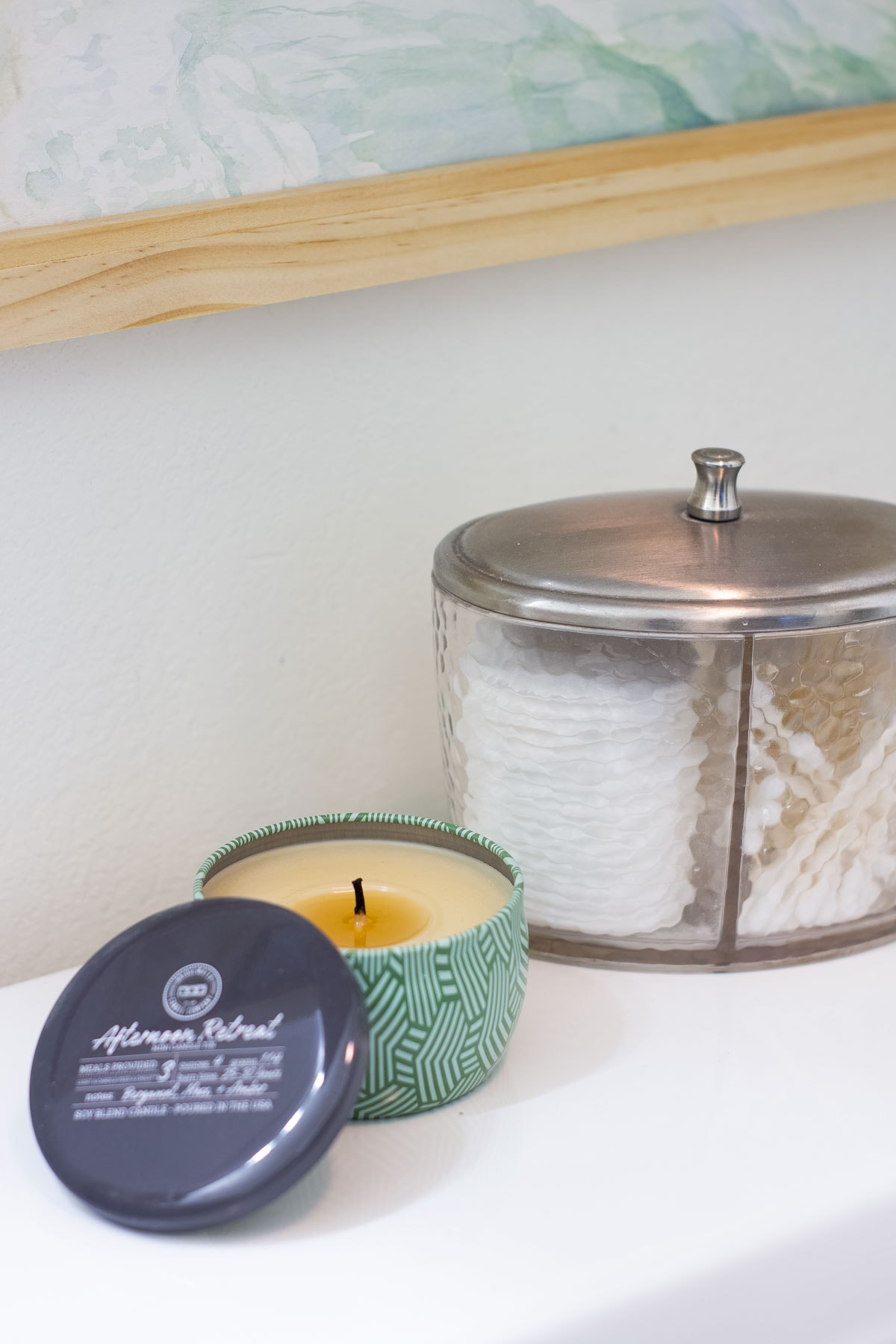 modern coastal bathroom makeover reveal closeup of candle and cotton ball holder