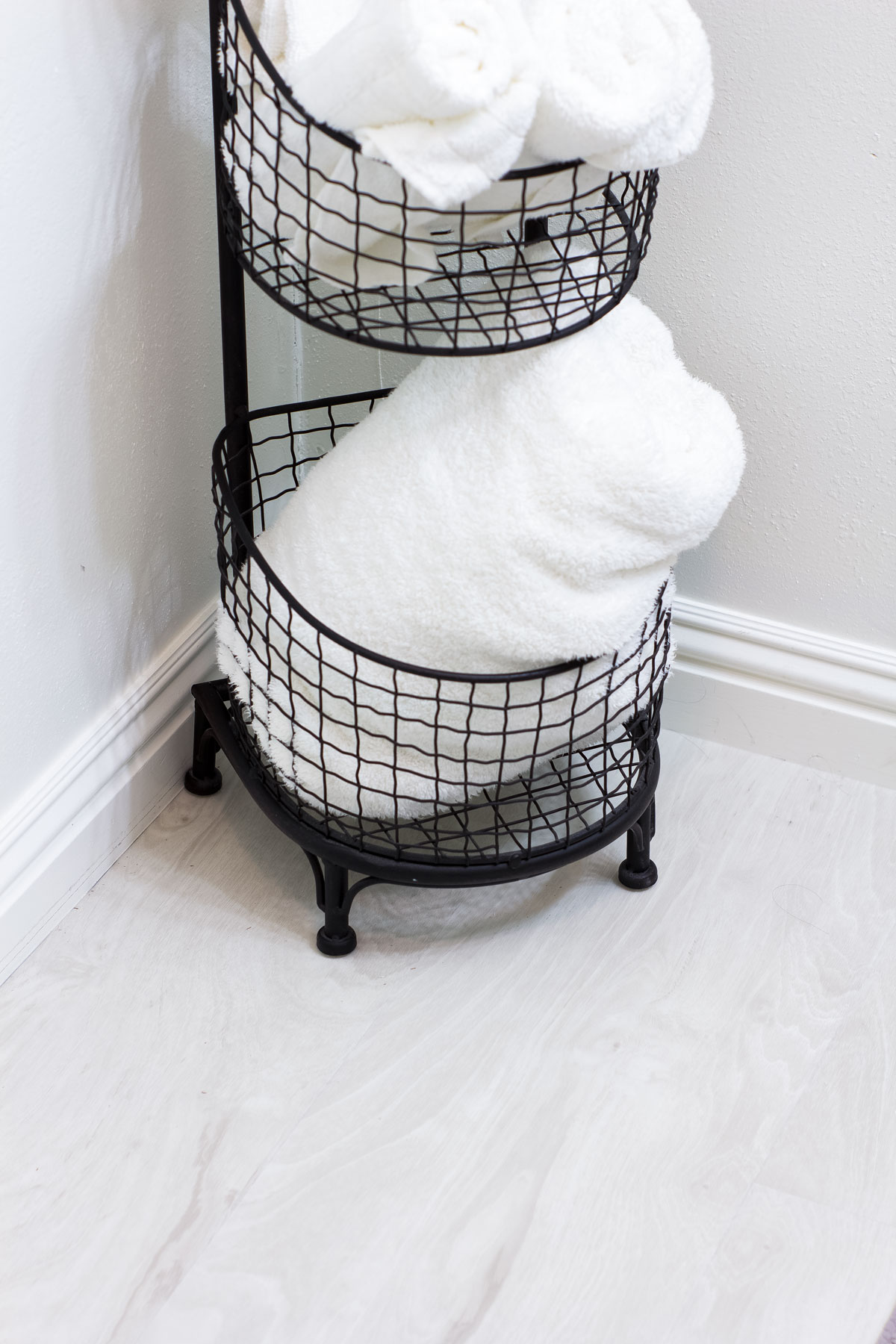 closeup of plank vinyl and black wire basket with white towel