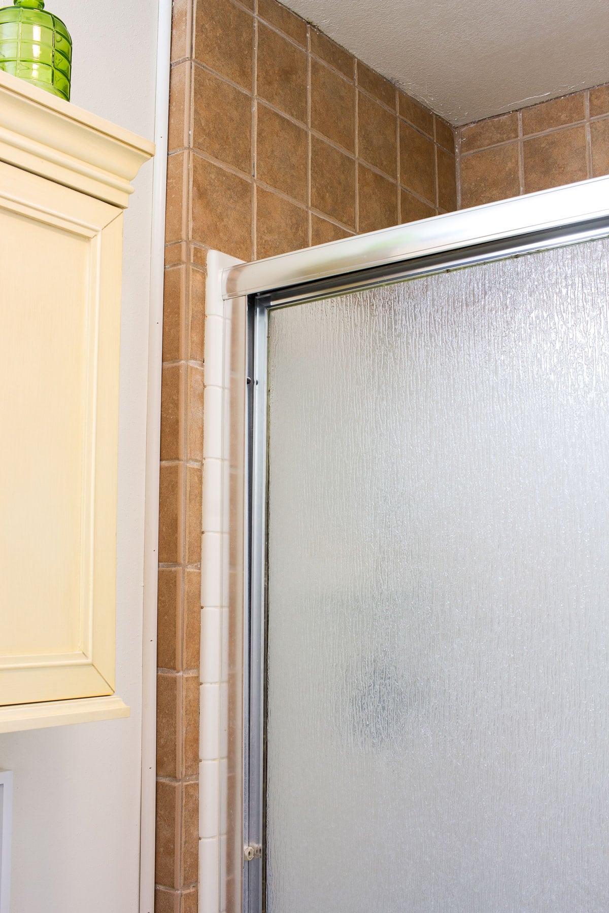 old beige tile shower surround and ugly shower door