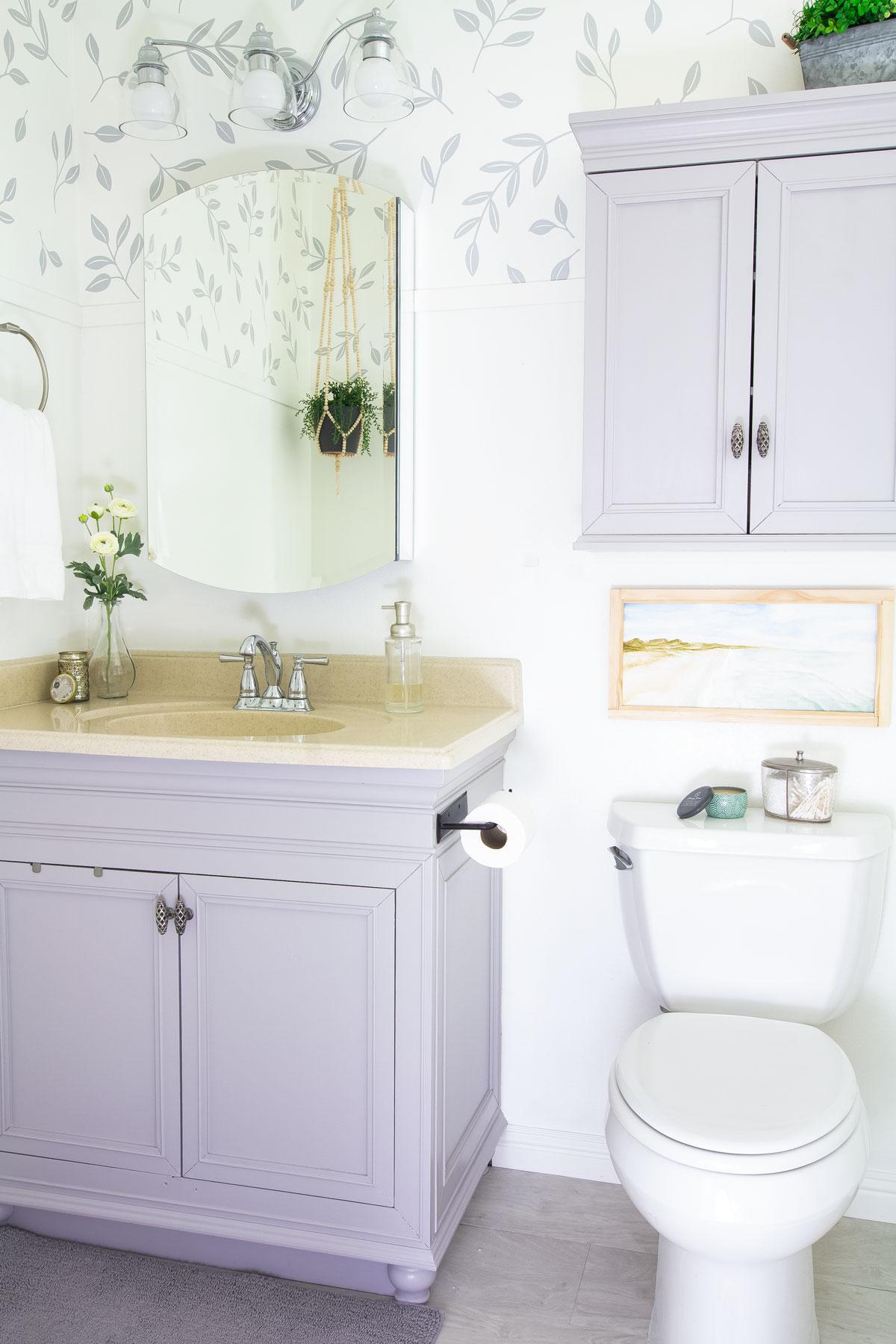 modern coastal bathroom makeover reveal bathroom gray vanity with leaf wallpaper and modern coastal elements