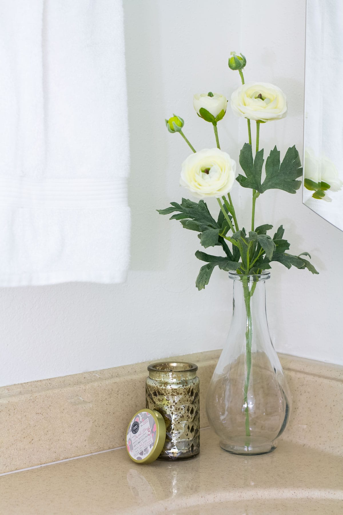 flowers in a vase with a candle on a bathroom counter