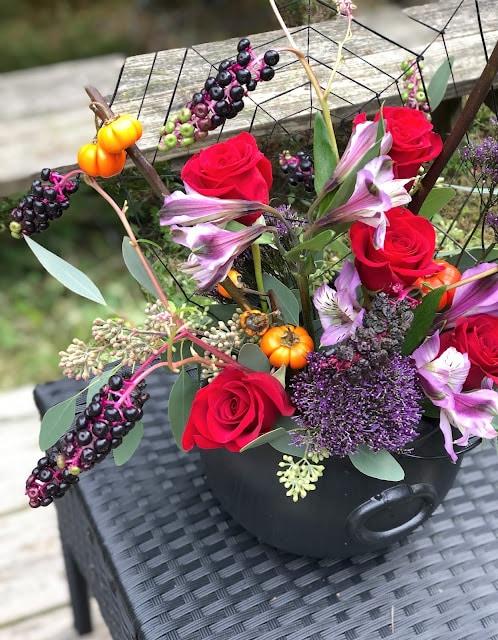 dramatic floral arrangement in a cauldron vase